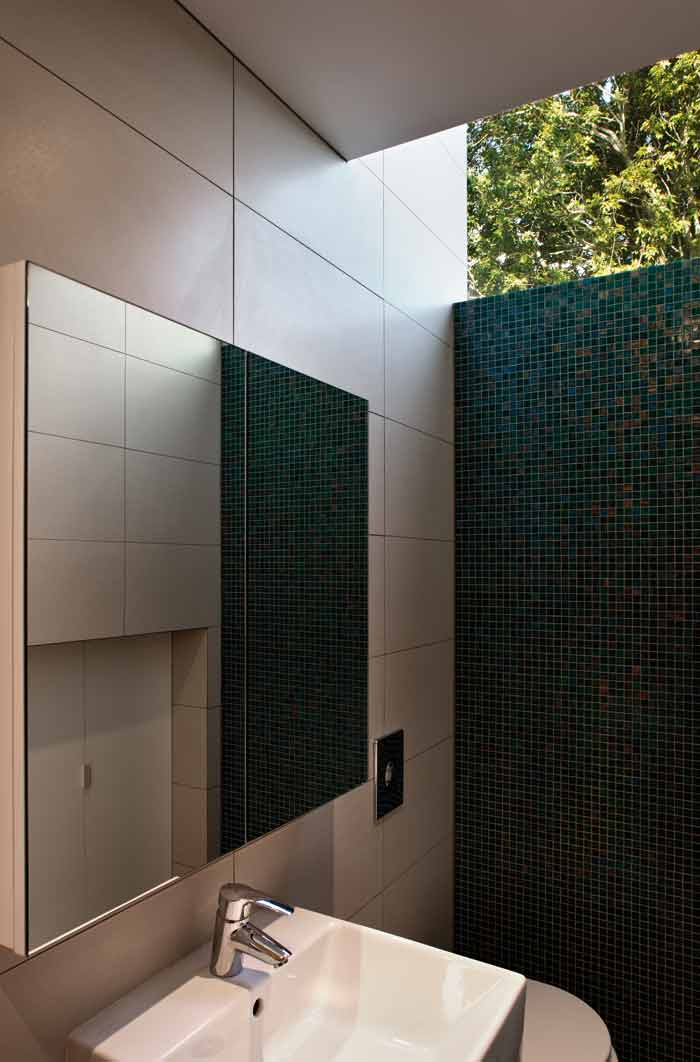 A high windows brings light to the subterranean bathroom.