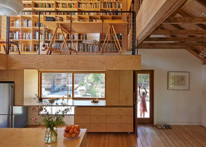 A study mezzanine floats above the kitchen, while a simple door on the right creates an informal entry into the house.