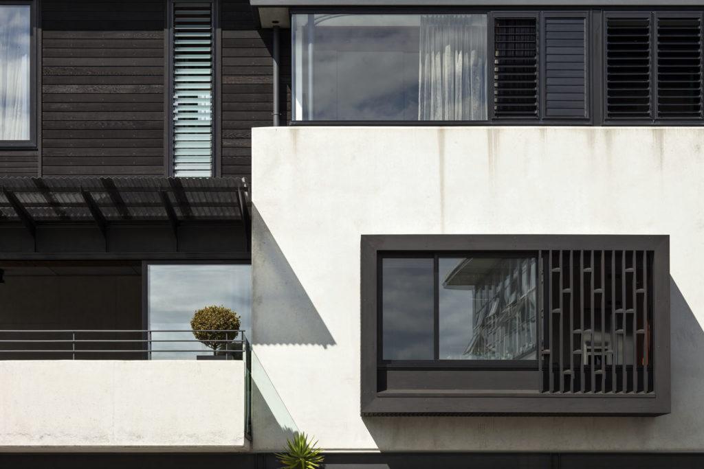 Gerrad Hall townhouse black cedar and pop-out windows soften concrete expanse